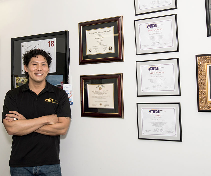 Russell F., ART physical therapist, standing by framed certifications.